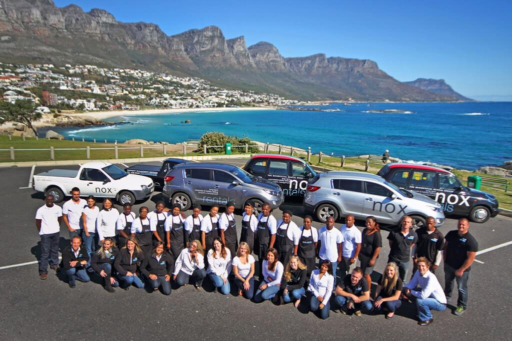 The team at the Maiden's Cove parking lot with Camps Bay and the Twelve Apostles mountain range in the background.
